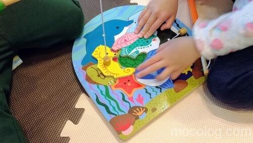 釣りのおもちゃでパズルをする娘